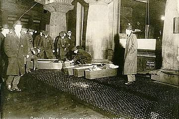 Picture shows police or fire officials placing Triangle Shirtwaist Company fire victims in coffins.
