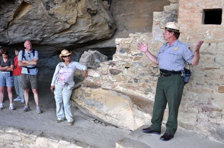 Parks Service ranger stands in front of American Indian ancient cave dwelling
