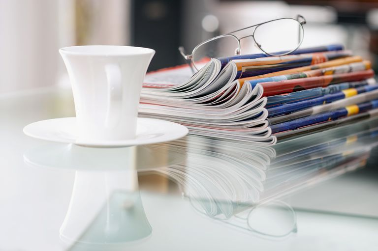 Still life with magazines, a coffee cup and a pair of glasses on a glass table