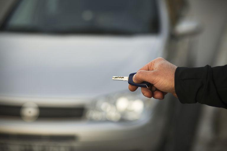 man holding keyless remote to vehicle