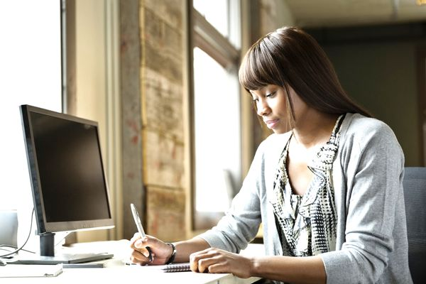 Young woman writing on notepad