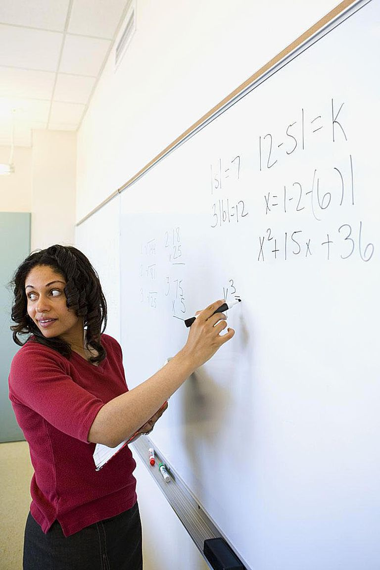 Hispanic female teacher writing on whiteboard