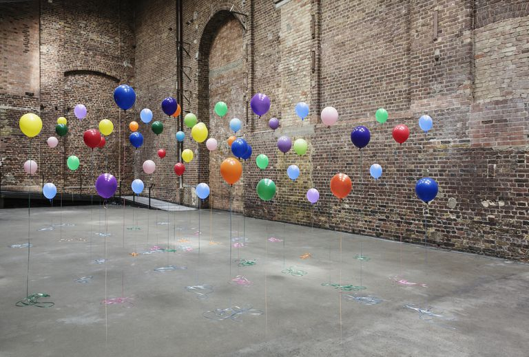 Colourful balloons in empty warehouse. Mixed metaphors.