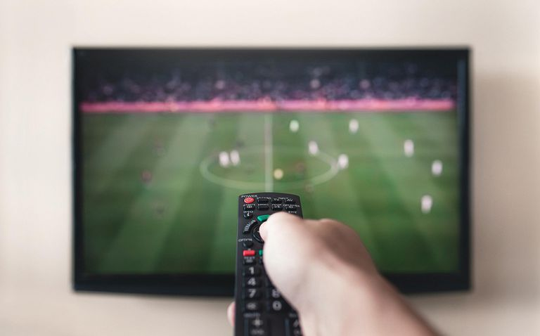Man holding remote control pointed at television