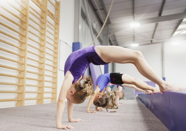 Young female gymnasts performing back bends onto a crash mat