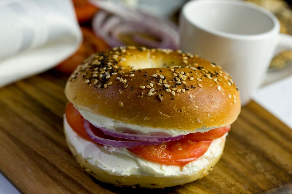 An everything bagel with cream cheese, tomato