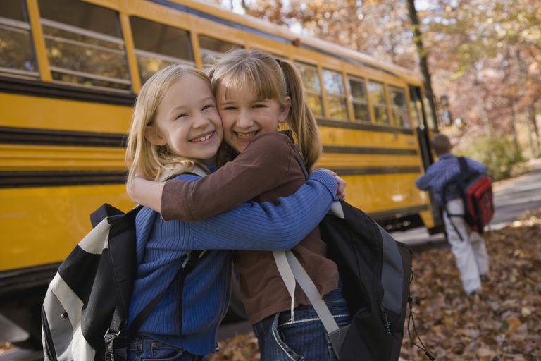 Two girls hugging in front of a school bus.
