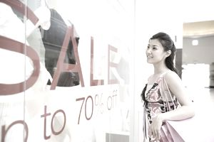 Woman looking at mannequins in boutique, smiling