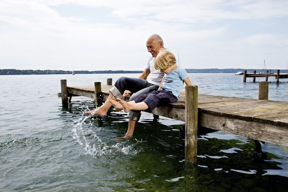 boy splashing with grandfather at lake