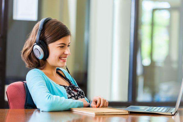 Preteen girl doing homework while listening to headphones