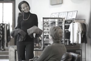 Saleswoman showing a man clothing