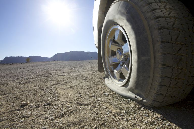 A low angle view of a vehicles flat tire in the desert