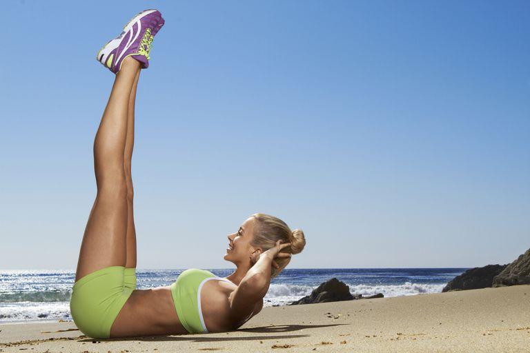 woman doing vertical crunch on the beach