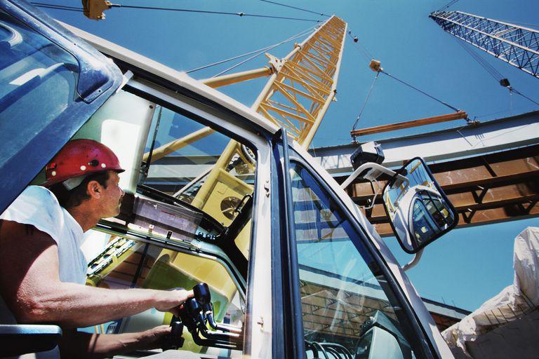 Crane operator lifting bridge beams