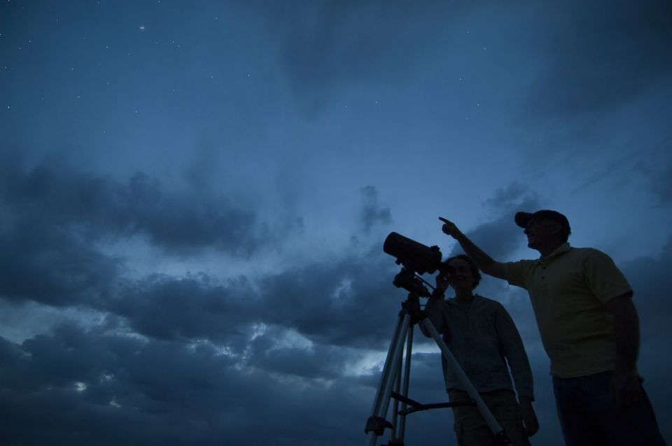 Couple using telescope on tripod