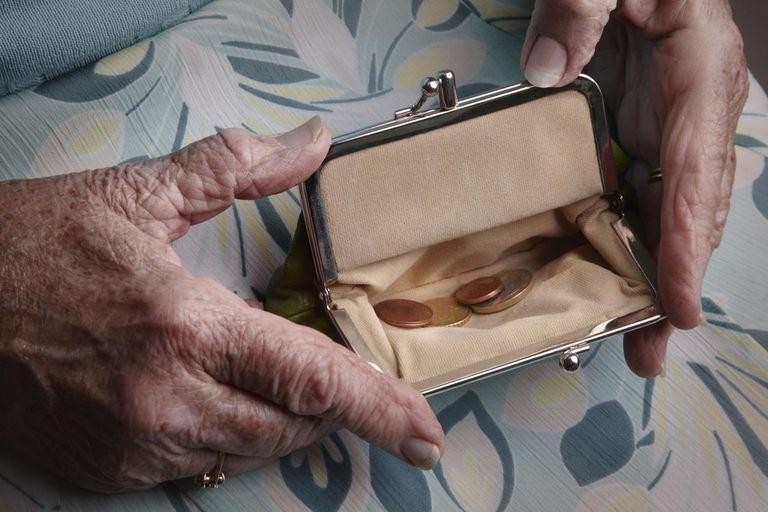 Senior woman holding open a coin purse.