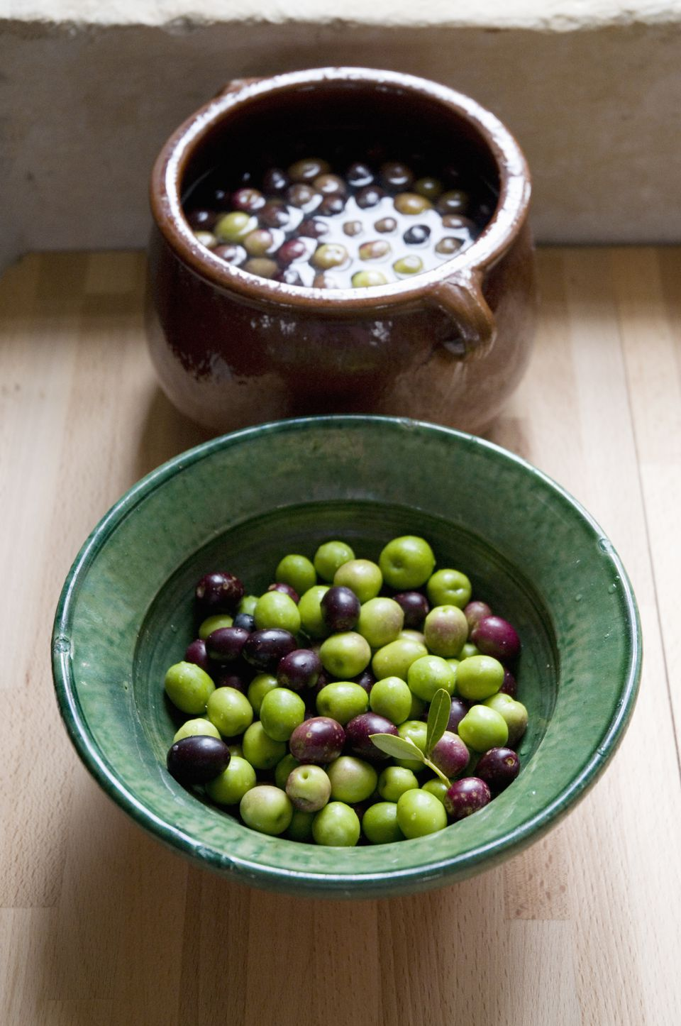 A bowl of raw olives(foreground) and a bowl of olives being cured in brine (background)