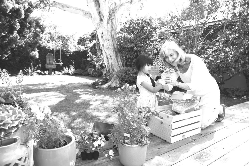 retired woman gardening with granddaughter