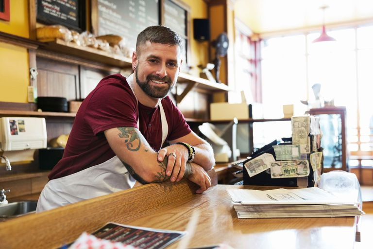 Male deli owner leaning on counter