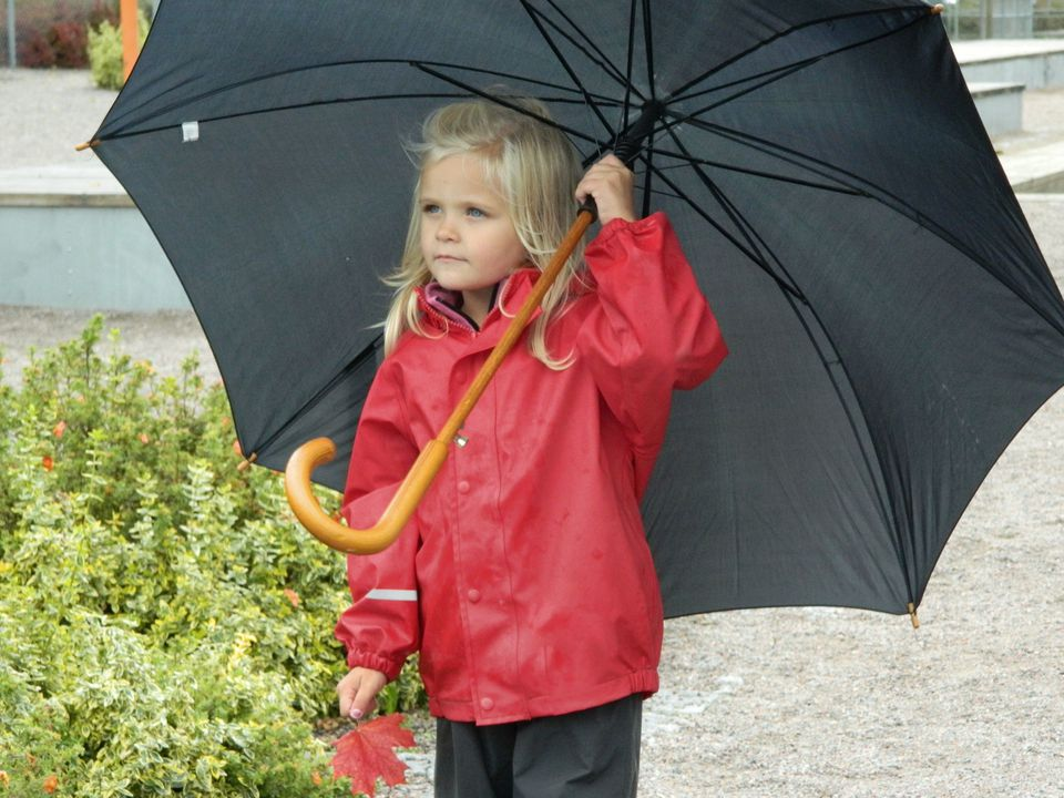 Girl Holding Umbrella While Standing On Road During Rainy Day