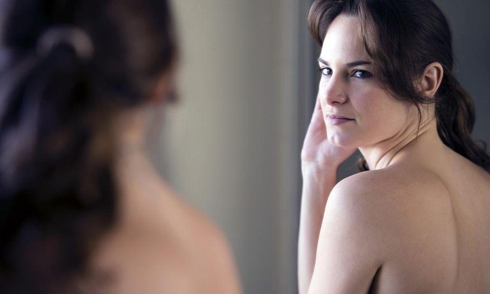 Nude Hispanic woman examining herself in mirror