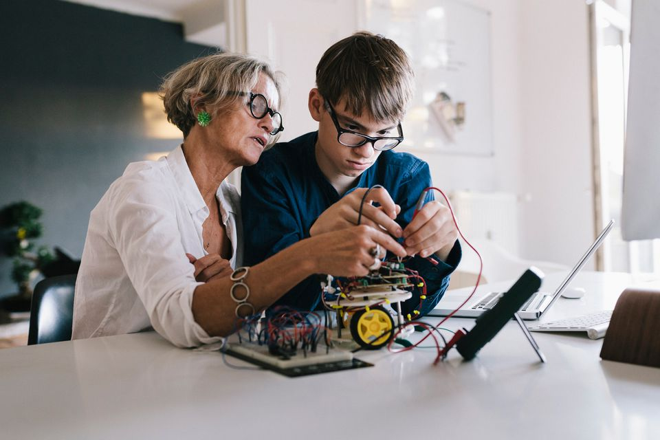 Mother and son using voltage meter