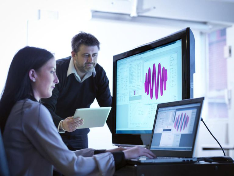 Workers using software to calibrate springs in office