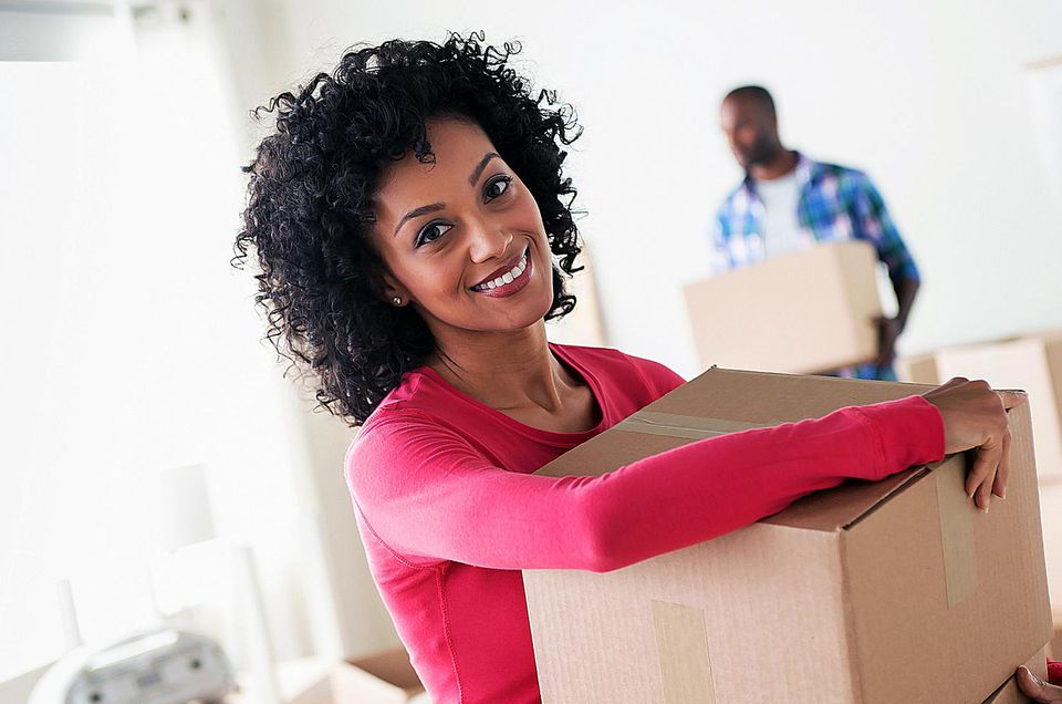 Happy woman holding a packed moving box with her husband in the background