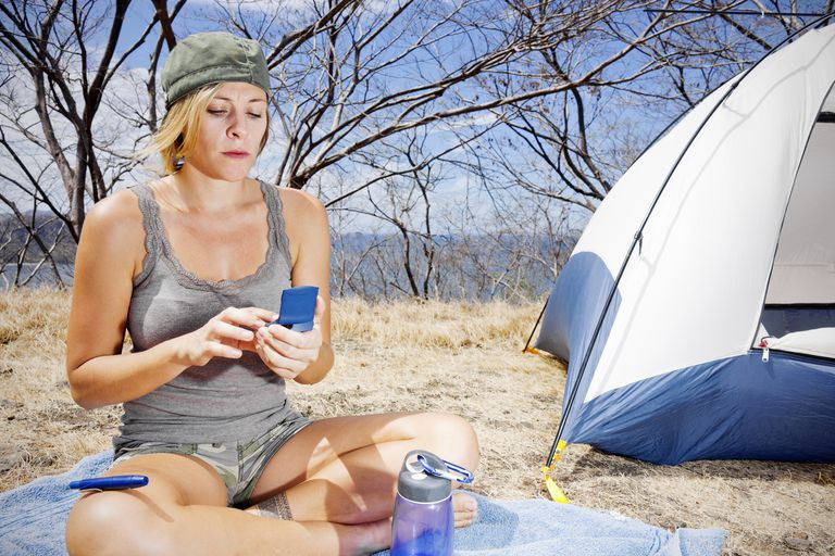 woman at campsite checking blood sugar