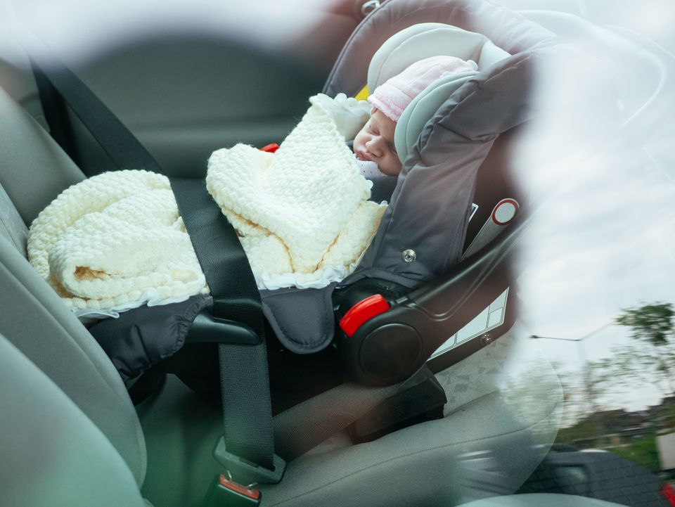 Cute two week old baby sleeping in car seat on back-seat of the car