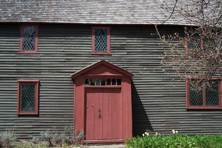 facade detail of very old house, dark clapboard, dark salmon-colored door and window trim, diamond-paned window glass