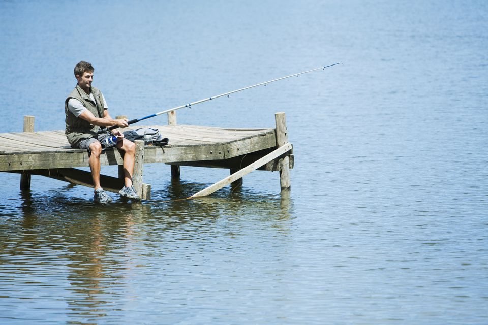 Man fishing from dock over lake