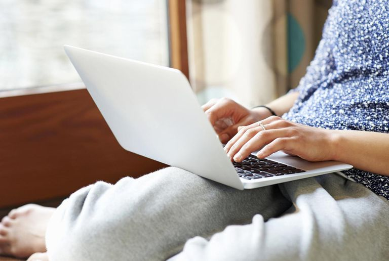Woman using laptop at home, close up