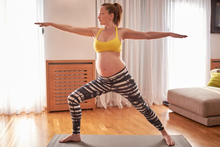 Pregnant woman doing Warrior 2 at home