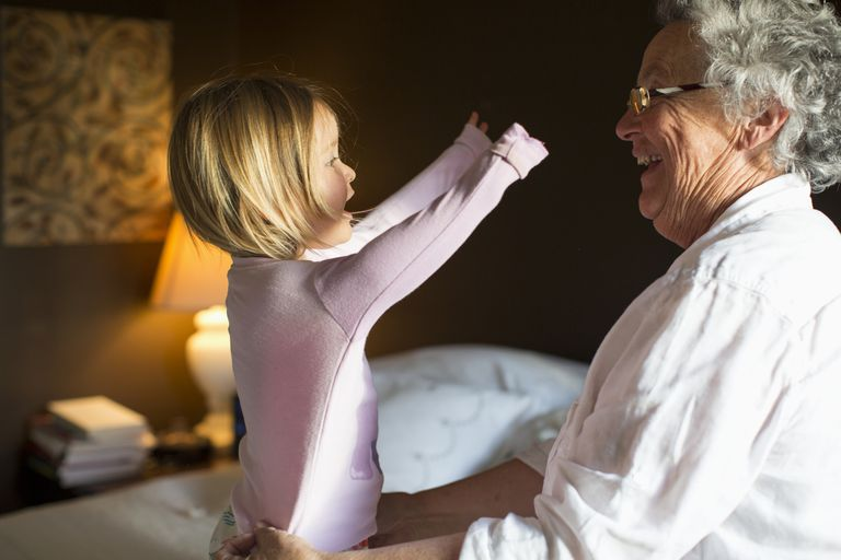 Grandmother getting granddaughter ready for bed