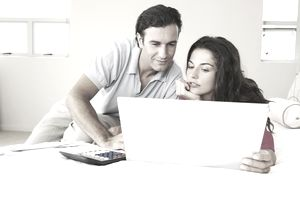 man and woman in front of laptop with calculator