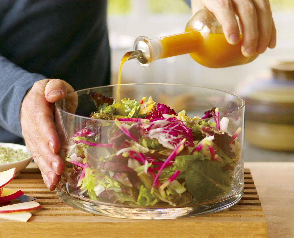 pouring orange vinaigrette on salad