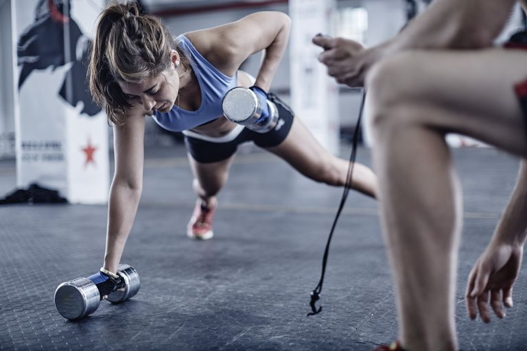 woman in plank position doing dumbell rows