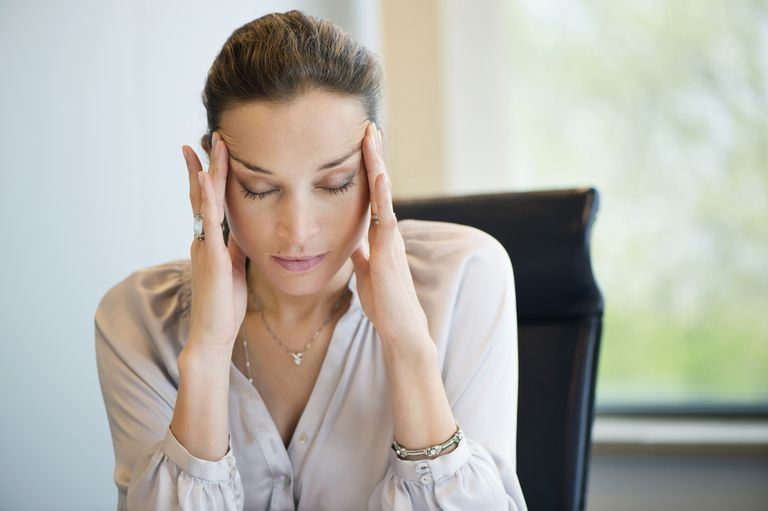 Close-up of a businesswoman suffering from a headache in an office