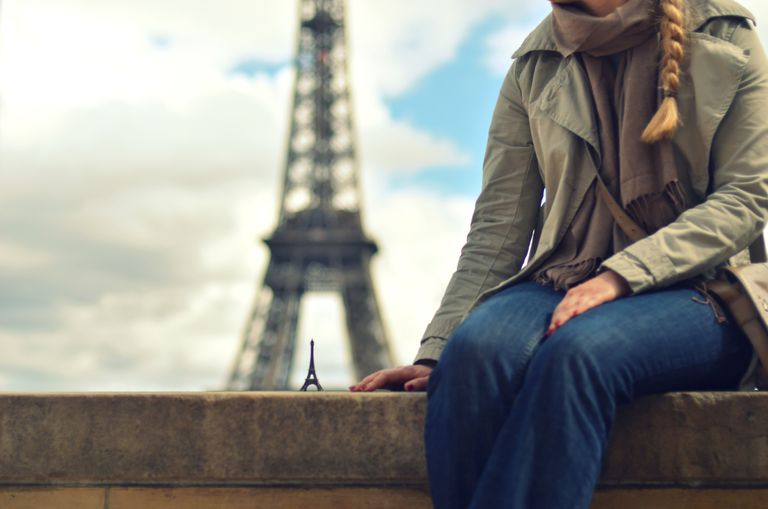 Woman in jeans sits near Eiffel Tower in Paris France