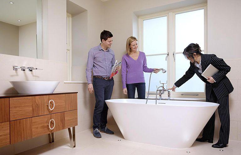Estate agent showing a fancy bathtub in a rental property.