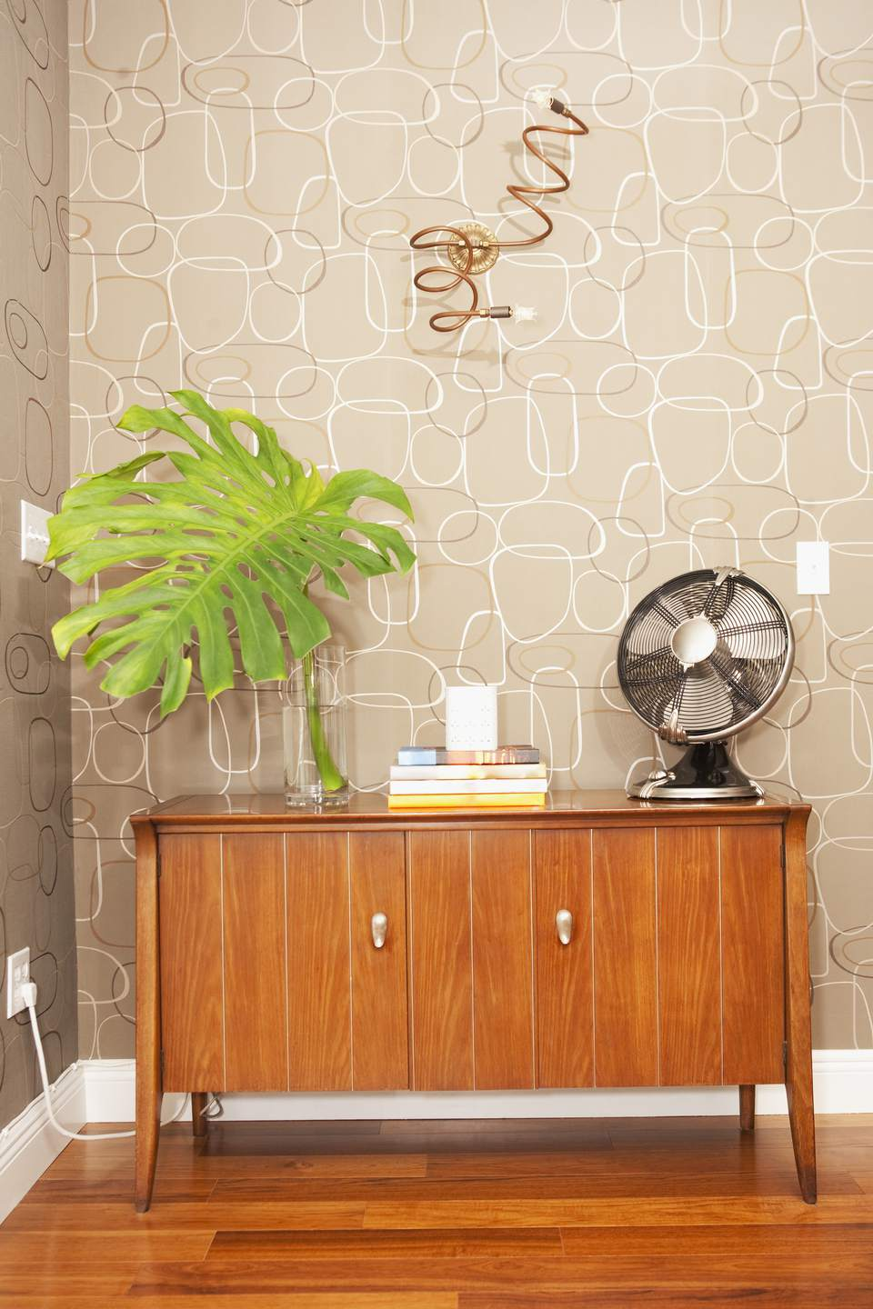 Electric fan with books on a sideboard