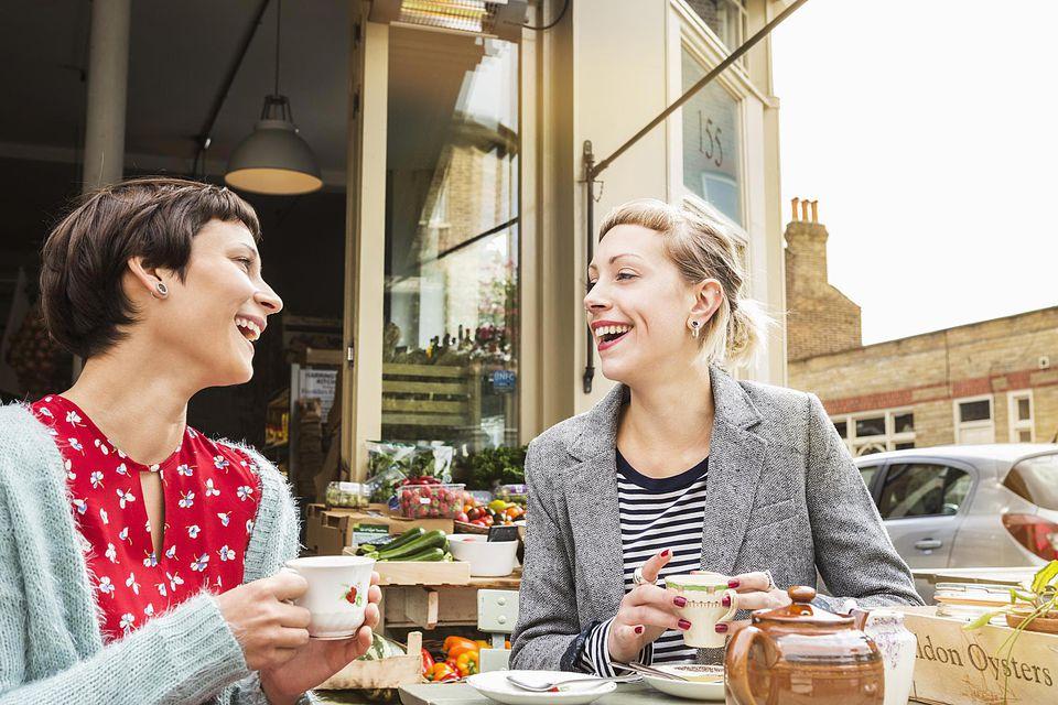 Female friends drinking tea outside farm shop