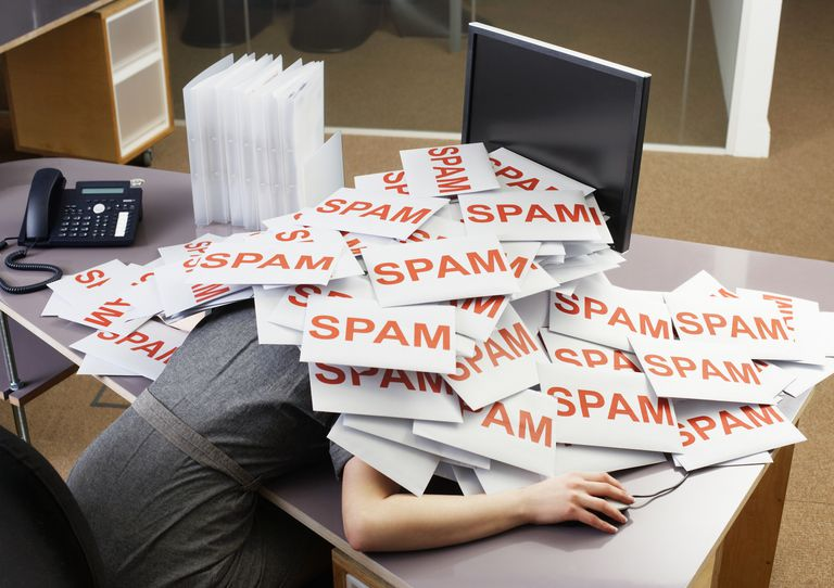 Woman at desk overwhelmed with spam email.
