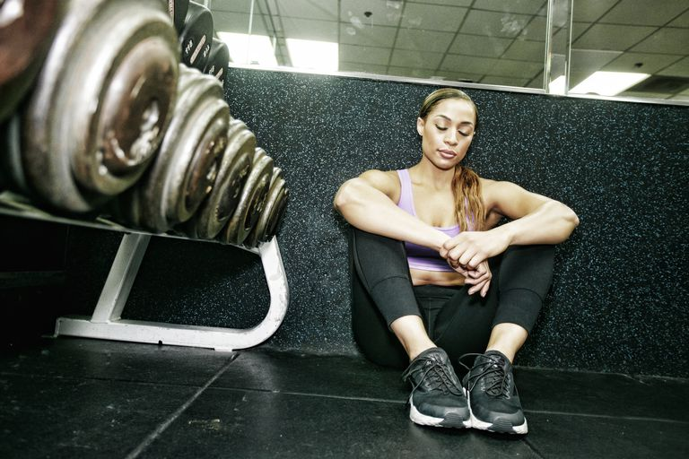 Mixed Race woman sitting on floor resting in gymnasium