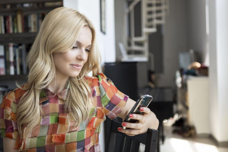 Portrait of beautiful woman looking at cell phone