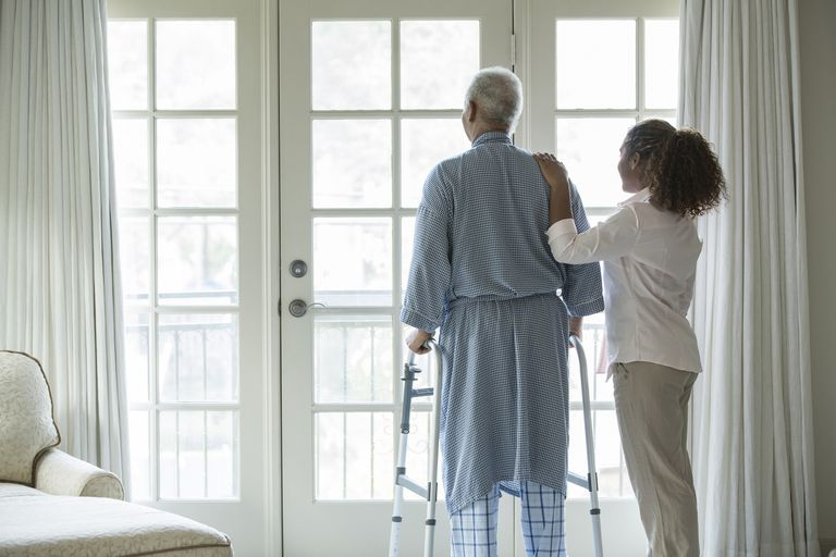 African American woman helping senior man with a walker