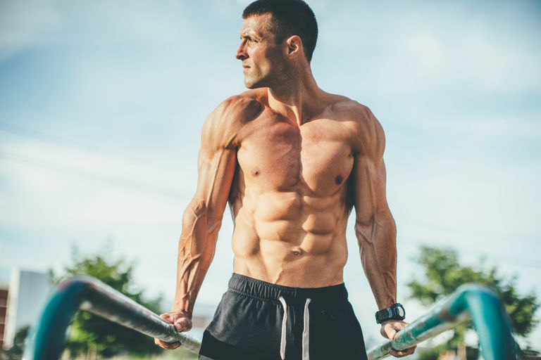 young muscular man doing triceps exercise outdoors
