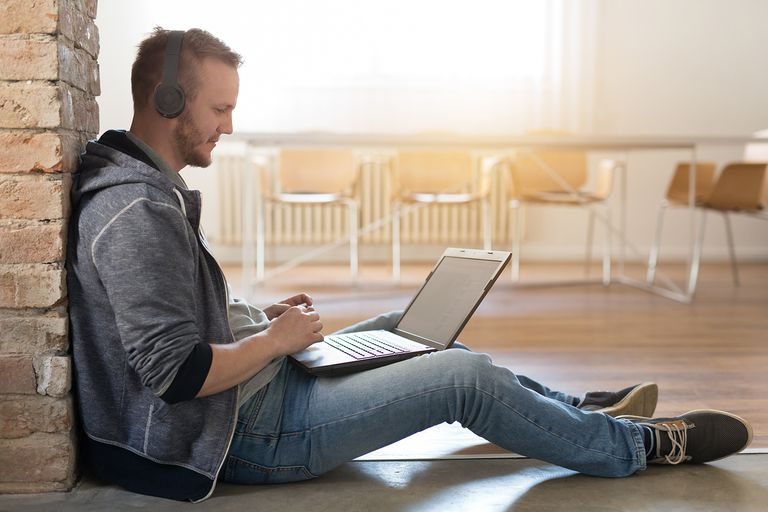 Young man with headphones and a laptop sitting at the office floor.