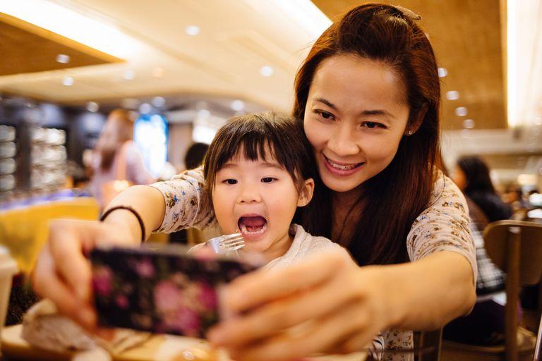 Mom & toddler girl taking selfie joyfully in cafe